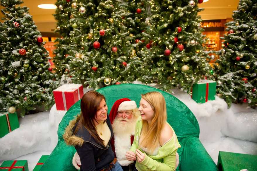 10th graders Miranda Browning and Jessica Curtin of Williamsburg, VA share a joke and sit on the lap of Michael Graham, who plays Santa at Tyson's Corner Center, Tyson's Corner, VA, Wednesday, December 14, 2011. This is Michael Graham's 22nd year as the Santa at Tyson's Corner Center where, from Thanksgiving to December, he can be seen greeting children and some young adults during the holiday season. (Andrew Harnik / The Washington Times)