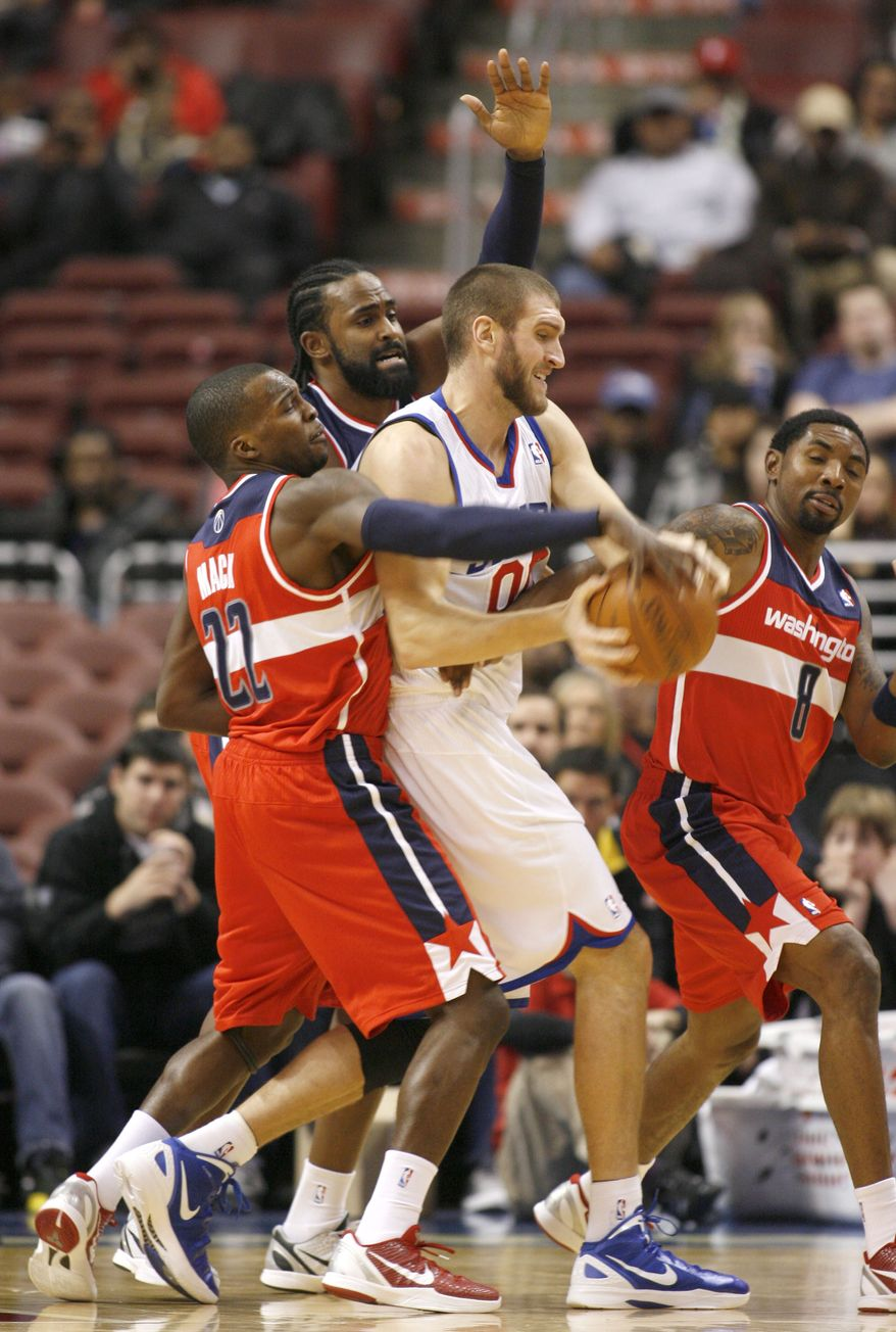 Washington Wizards' Shelvin Mack (22) Ronny Turiaf and Roger Mason Jr defend as Philadelphia 76ers' Spencer Hawes (00) looks to pass in the first half of a preseason NBA game Tuesday, Dec. 20, 2011, in Philadelphia. (AP Photo/H. Rumph Jr )