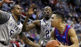 American's Blake Jolivette, right, drives against Georgetown's Markel Starks (5) and Jason Clark (21) during the first half of an NCAA college basketball game, Saturday, Dec. 17, 2011, in Washington. Georgetown won 81-55. (AP Photo/Luis M. Alvarez)