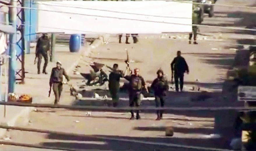 Soldiers move down a street in Daraa, Syria, in this video scene shown on the Internet. Amateur video emerged Monday from Syria that purported to show ongoing violence in the country. Scenes could not be independently verified as showing the Syrian government brutalizing its people. (Associated Press)