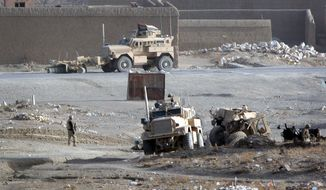 A Polish military armored vehicle (right) was destroyed by a roadside bomb in Ghazni, Afghanistan, southwest of Kabul, on Wednesday, Dec. 21, 2011. Five Polish soldiers were killed in the blast. (AP Photo/Rahmatullah Nikzad)