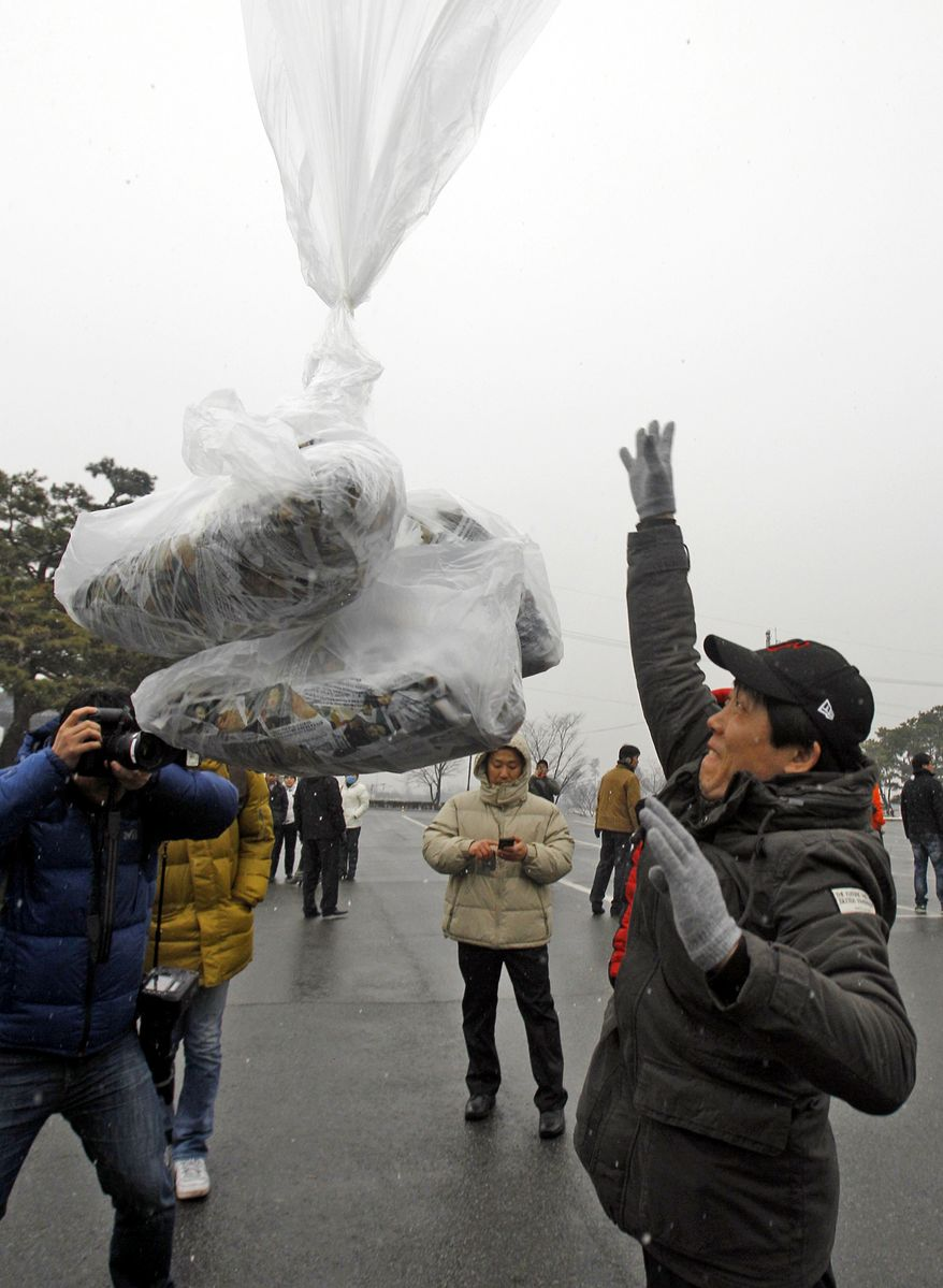 North Korean defector Park Sang-hak (right) releases a balloon bearing leaflets condemning North Korean leader Kim Jong-il and his son Kim Jong-un during a demonstration against the North at the Imjingak Pavilion near the border village of Panmunjom in Paju, South Korea, on Wednesday, Dec. 21, 2011. (AP Photo/Lee Jin-man)