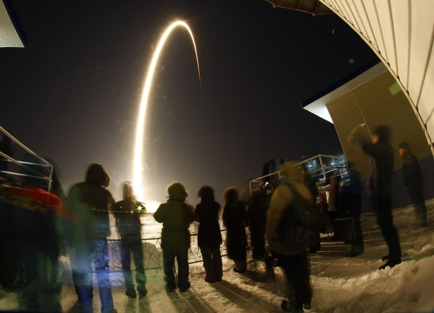 In this photo taken with a fisheye lens and with long-time exposure, people watch the launch of the Soyuz-FG rocket booster with the Soyuz TMA-03M space ship carrying a new crew to the International Space Station, at the Russian-leased Baikonur cosmodrome, Kazakhstan, Wednesday, Dec. 21, 2011. The Russian rocket carries U.S. astronaut Donald Pettit, Russian cosmonaut Oleg Kononenko and Netherlands' astronaut Andre Kuipers. (AP Photo/Dmitry Lovetsky)