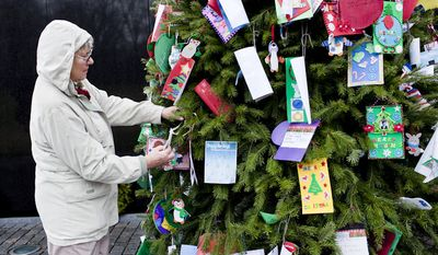 "Shirley Salchert of Vancouver, British Columbia, replaces an ornament that fell off of the Christmas tree at the Vietnam Veterans Memorial in Washington on Wednesday, Dec. 21, 2011. ""It's a moving place to be,"" said Ms. Salchert, on a visit with her son, who works for the North American Aerospace Defense Command. (T.J. Kirkpatrick/The Washington Times)"