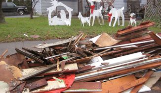 Flood debris awaits pickup in front of a Christmas manger scene Wednesday at a West Pittston, Pa., home. Months after a tropical storm caused Susquehanna River flooding, many will be out of their homes for Christmas. (Associated Press)