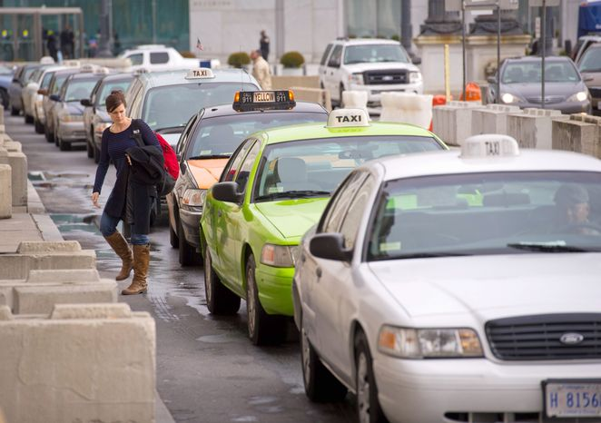 **FILE** A woman walks through a line of cabs outside of Union Station in Washington, D.C. (Rod Lamkey Jr./The Washington Times)
