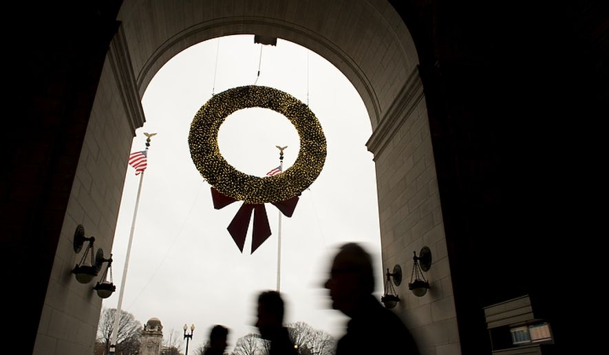 People open their umbrellas under one of three Christmas wreaths on display at Union Station in Washington on Tuesday, Dec. 6, 2011, as a steady light rain falls. (Rod Lamkey Jr./The Washington Times) ** FILE **