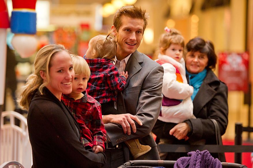 Amber (left) and Drew (center) Fearson of Chantilly wait in line with their 2-year-old son, Tanner (second from left), and 1-year-old Reagan (third from left) to get a chance to visit with Santa, played by Michael Graham, at Tysons Corner Center in Tysons Corner on Wednesday, Dec. 14, 2011. (Andrew Harnik/The Washington Times)