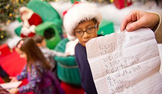 Benjamin Hawley (center), 9, of Arlington gives his Christmas list back to his mother after visiting with Santa, played by Michael Graham, at Tysons Corner Center in Tysons Corner on Wednesday, Dec. 14, 2011. (Andrew Harnik/The Washington Times)