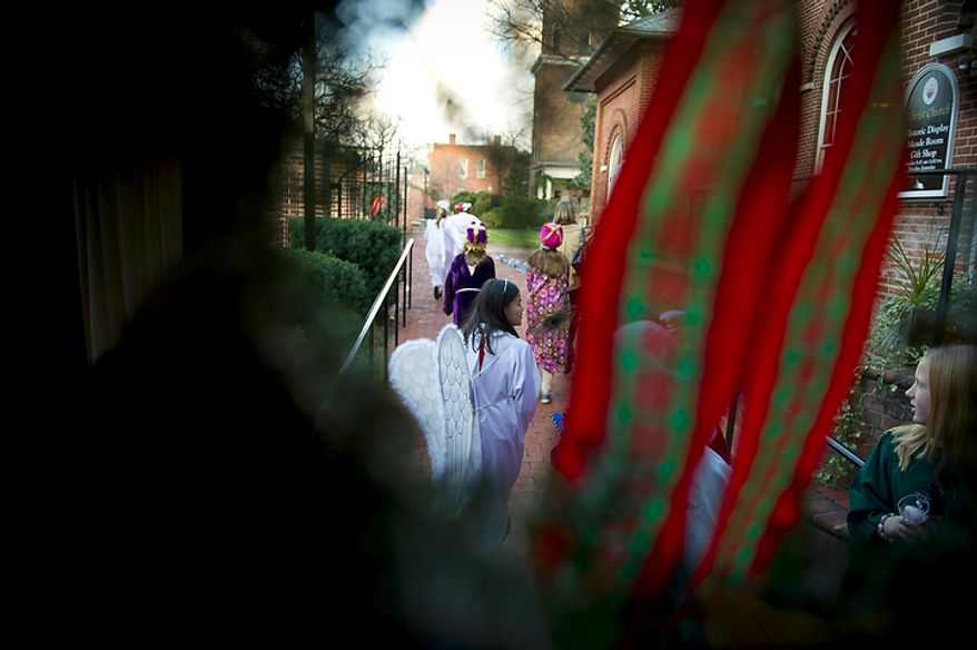 Children make their way along the path en route to the Christ Church, where President George Washington once worshipped, for their performance in the Nativity scene of a Christmas pageant in Alexandria on Sunday, Dec. 18, 2011. (Rod Lamkey Jr./The Washington Times)