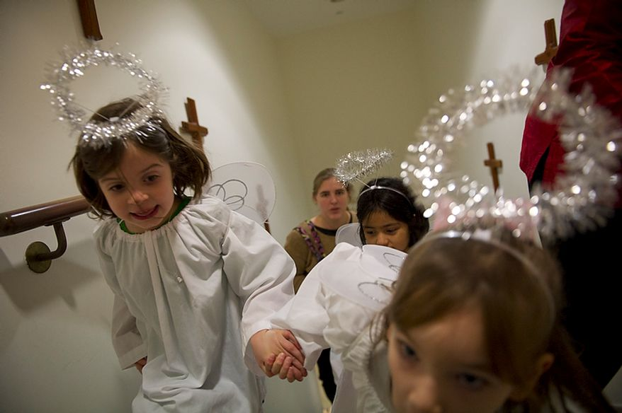 Children playing angels run up the stairs at Christ Church, where President George Washington worshipped, to perform in the Nativity scene of the church's Christmas pageant on Sunday, Dec. 18, 2011, in Alexandria. (Rod Lamkey Jr./The Washington Times)