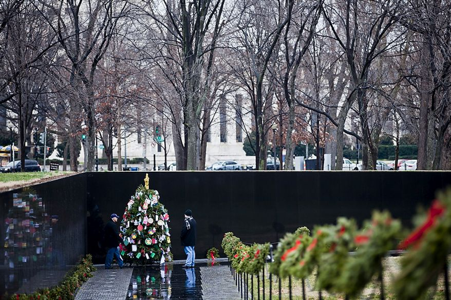 "David Ingram (left) of Jacksonville, Fla., and his son Ty look at the Christmas tree in the Vietnam Veterans Memorial in Washington on Wednesday, Dec. 21, 2011. Mr. Ingram, a retired U.S. Army Reserve member, said, ""This is my generation ... it just amazes me how many people died."" (T.J. Kirkpatrick/The Washington Times)"