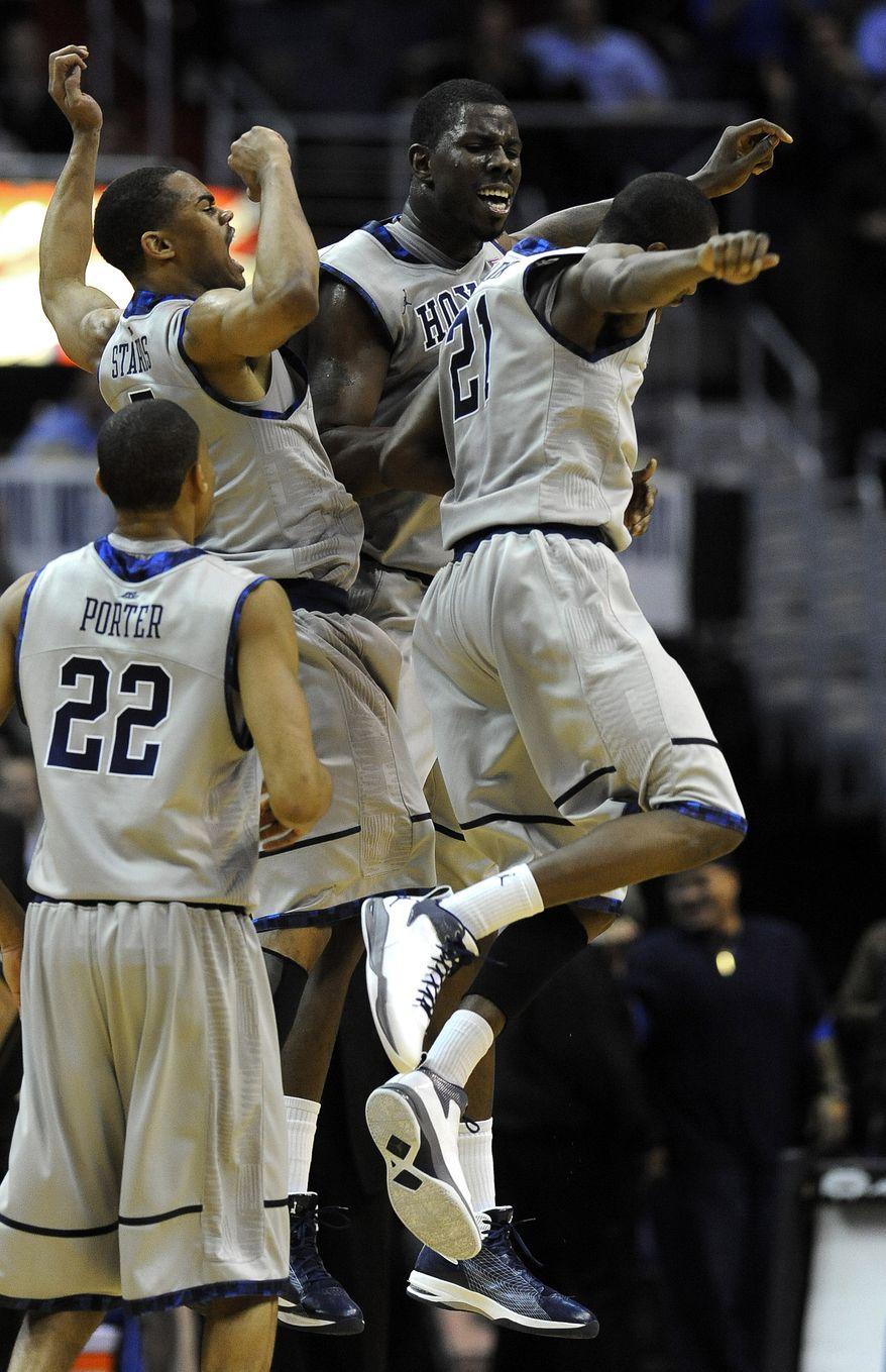 Georgetown center Henry Sims, background center, and fellow teammates Markel Starks, left, and Jason Clark (21) jump along with Otto Porter (22) after Sims scored a basket just before the end of first half Thursday, Dec. 22, 2011, in Washington. Georgetown went on to defeat Memphis 70-59. (AP Photo/Richard Lipski)