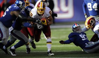 Washington Redskins running back Roy Helu is tackled by New York Giants defensive tackle Rocky Bernard, left, and defensive end Jason Pierre-Paul, center, during the first quarter, Sunday, Dec. 18, 2011, in East Rutherford, N.J. (AP Photo/Bill Kostroun)