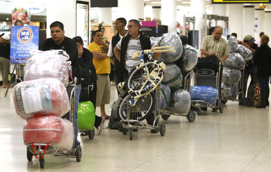 Travelers wait in line with their luggage at Miami International Airport before traveling Cuba, Monday, Dec. 19, 2011, in Miami. As the holidays approach this year, thousands of Cuban-Americans are taking advantage of the Obama administration's relaxed travel regulations to return to the island. (AP Photo/Lynne Sladky)