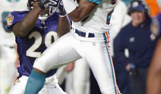 FILE - In this Nov. 17, 2002, file photo, Miami Dolphins' Patrick Surtain intercepts a pass intended for Baltimore Ravens' Chester Taylor, rear, in the third quarter of an NFL football game in Miami. Surtain is one of nearly two dozen former NFL players that are suing the league over severe and permanent brain damage they say is linked to concussions suffered on the job. The complaint, filed on Thursday, Dec. 22, 2011, follows a similar one in Atlanta this week. (AP Photo/Gary I. Rothstein, File)