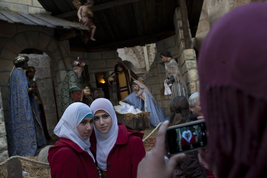Two Palestinian Muslim women pose for a snapshot in front a nativity scene inside the Church of Nativity, believed by many to be the birthplace of Jesus Christ, in the West Bank town of Bethlehem, Saturday, Dec. 24, 2011. (AP Photo/Bernat Armangue)