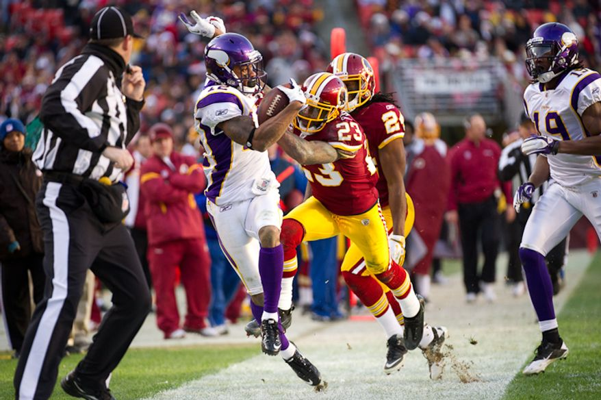 Minnesota Vikings wide receiver Percy Harvin (12) is pushed out of bounds by Washington Redskins cornerback DeAngelo Hall (23) after a 31 yard gain in the third quarter as the Washington Redskins take on the Minnesota Vikings at Fedex Field, Landover, MD, Saturday, December 24, 2011. (Andrew Harnik / The Washington Times)