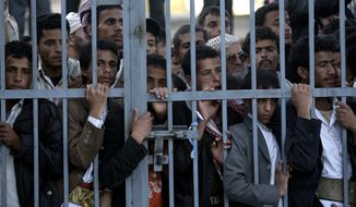 Protestors stand behind the gate of a field hospital to watch wounded demonstrators being carried from the site of clashes with security forces, in Sanaa, Yemen, Saturday, Dec. 24, 2011. More than 100,000 protesters who entered Yemen's capital Saturday after a 4-day march from another city were attacked by elite troops loyal to outgoing President Ali Abdullah Saleh. (AP Photo/Hani Mohammed)