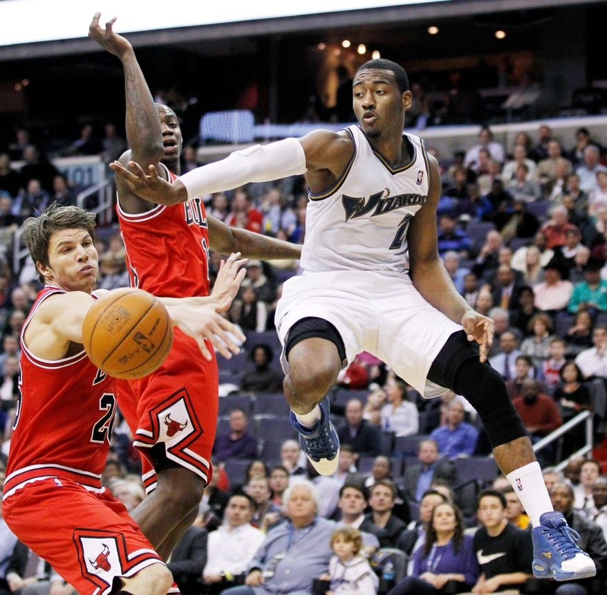 Washington Wizards' John Wall (2) passes the ball from under the basket while Chicago Bulls Kyle Korver, left, and Ronnie Brewer defend during the second half of an NBA basketball game in Washington, Monday, Feb. 28, 2011. Bulls won 105-77. (AP Photo/Manuel Balce Ceneta)