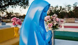 A blue statue of the Virgin Mary is surrounded by yellow, green and red grave markers at the Southdown Cemetery in Houma, La. Local lawmaker Alvin Tillman is pushing for legislation that would make it illegal to paint a tomb anything but white. (Houma Courier via Associated Press)