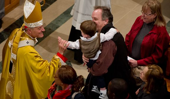 The Archbishop of Washington Cardinal Donald Wuerl greets a young worshiper during Christmas Mass held at the Basilica of the National Shrine of the Immaculate Conception on Christmas Day, Washington, D.C., Sunday, Dec. 25, 2011. (Andrew Harnik/The Washington Times)