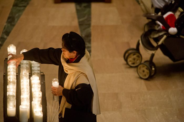 A woman lights a candle during Christmas Mass celebrated by Archbishop of Washington Cardinal Donald Wuerl at the Basilica of the National Shrine of the Immaculate Conception on Christmas Day, Washington, D.C., Sunday, Dec. 25, 2011. (Andrew Harnik/The Washington Times)