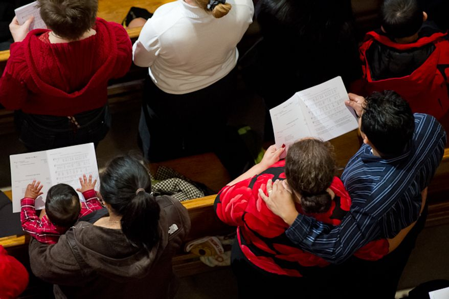 Worshippers follow along with the service during Christmas Mass celebrated by Cardinal Donald Wuerl, archbishop of Washington, at the Basilica of the National Shrine of the Immaculate Conception on Christmas Day, Sunday, Dec. 25, 2011, in Washington. (Andrew Harnik/The Washington Times)