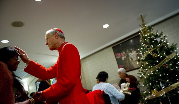 Archbishop of Washington Cardinal Donald Wuerl blesses Rita George of Silver Spring, Md., at a Christmas dinner in the basement of the Basilica of the National Shrine of the Immaculate Conception following Christmas Mass, Washington, D.C., Sunday, Dec. 25, 2011. (Andrew Harnik/The Washington Times)