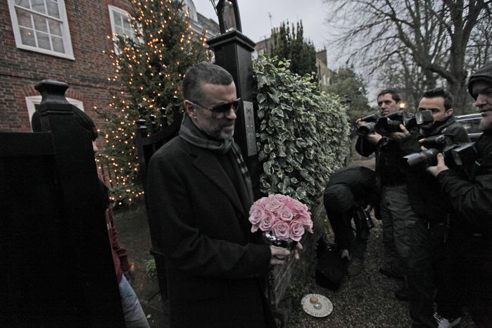 British singer George Michael leaves his house in north London, Friday, Dec. 23, 2011. Michael, short of breath and appearing weak, said Friday he has recovered from a life-threatening bout with pneumonia that kept him in a Vienna hospital for a month. (AP Photo/Lefteris Pitarakis)