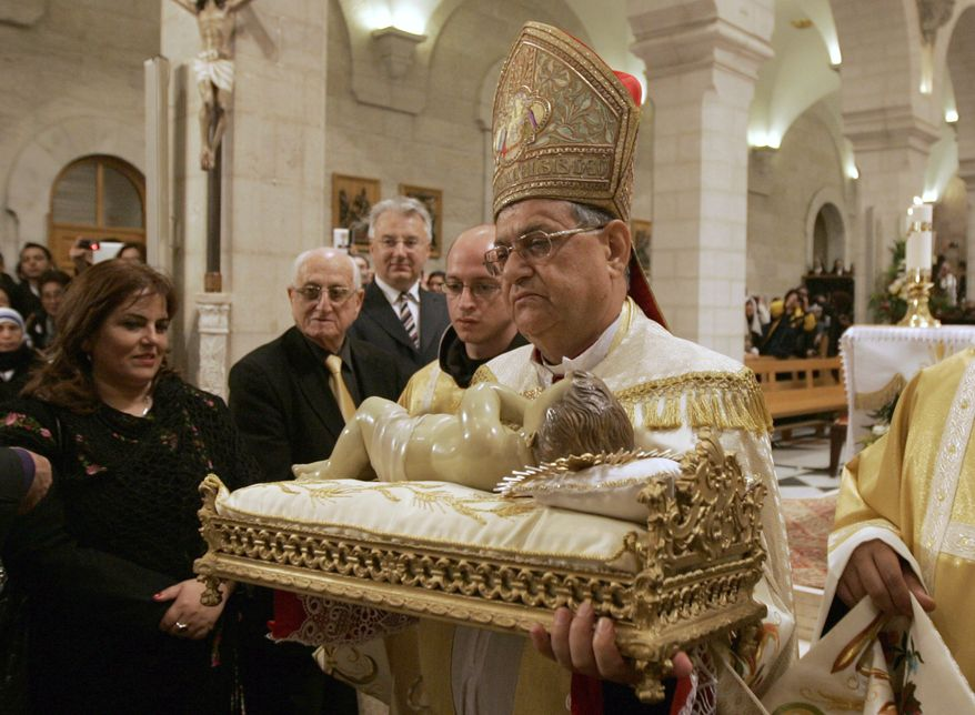 Archbishop Fouad Twal, the Latin patriarch of Jerusalem, carries a statuette of baby Jesus during the Christmas midnight Mass at the Church of the Nativity, traditionally believed to be the birthplace of Jesus Christ, in the West Bank town of Bethlehem early on Sunday, Dec. 25, 2011. (AP Photo/Majdi Mohammed, Pool)