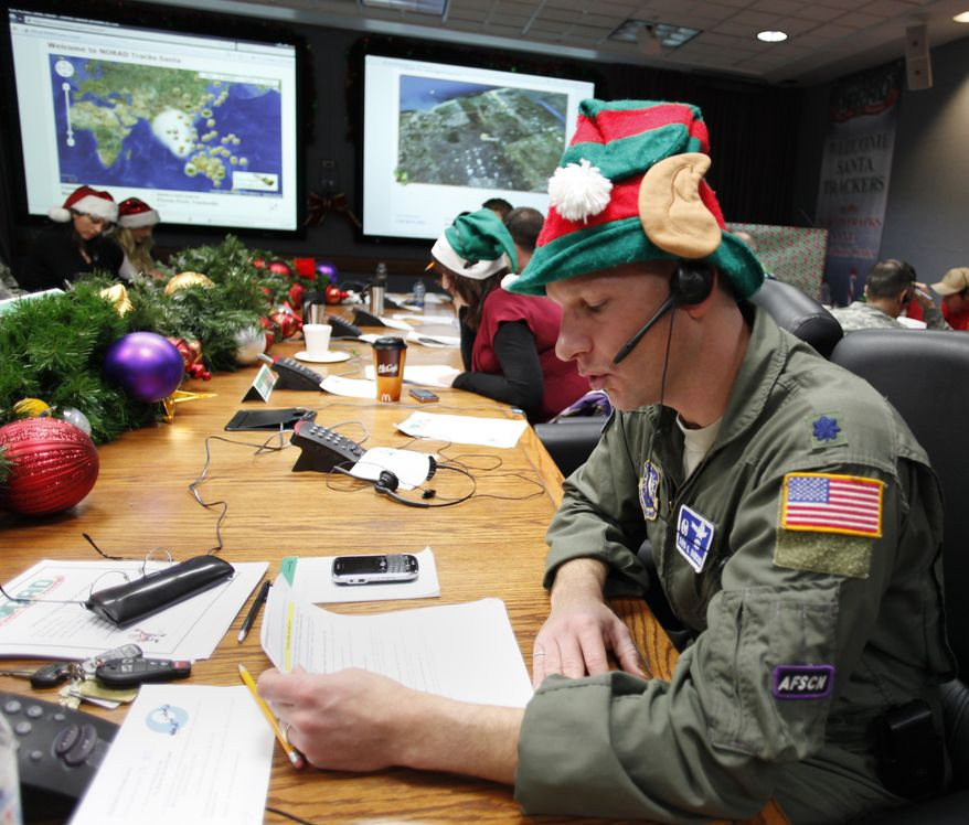 ** FILE ** Air Force Lt. Col. David Hanson of Chicago takes a phone call from a child in Florida at the Santa Tracking Operations Center at Peterson Air Force Base near Colorado Springs, Colo., on Dec. 24, 2010. (AP Photo/Ed Andrieski)