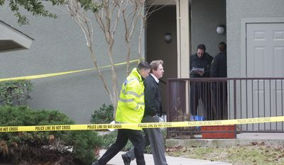 Grapevine police investigate the scene where they found seven people dead outside Fort Worth in Grapevine, Texas, Sunday, Dec. 25, 2011. Four women and three men who police believe to be related were found apparently shot, and authorities said they believe the shooter is among the dead. (AP Photo/The Dallas Morning News, Michael Ainsworth)