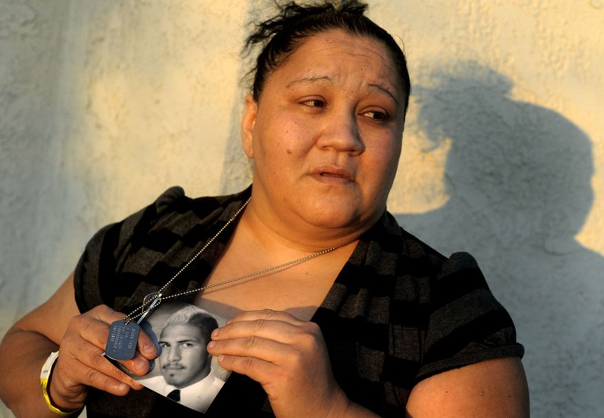 Suzanne Sullivan holds a photo of her son, Army Spec. Christopher Sullivan, outside her home in San Bernardino, Calif., on Saturday, Dec. 24, 2011. (AP Photo/The San Bernardino Sun, Gabriel Luis Acosta)