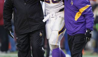 Minnesota Vikings running back Adrian Peterson (28) is helped off the field after an injury during the second half against Washington Redskins in Landover, Md., Saturday, Dec. 24, 2011. (AP Photo/Evan Vucci)