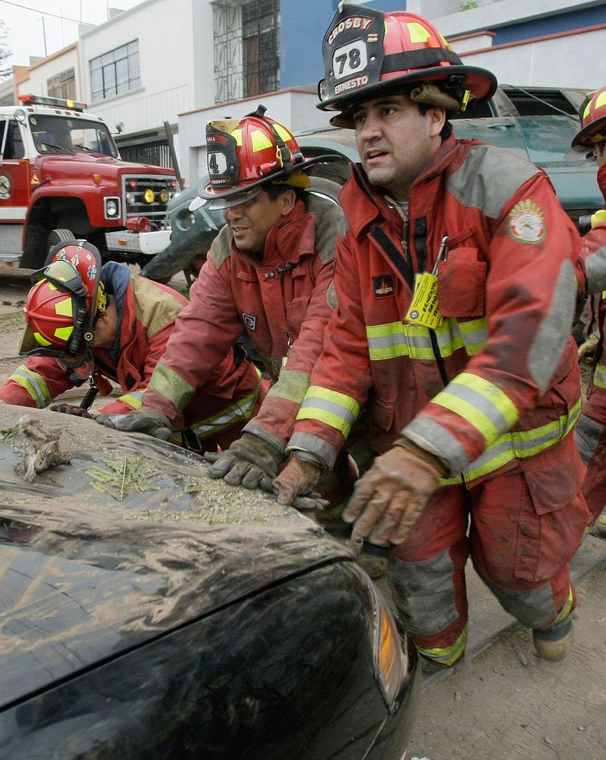 Volunteer firefighters from the Lima Four fire station push a car that was involved in a traffic accident. Peru's firefighters are so cash-strapped and ill-equipped that vital lifesaving equipment too often fails at a burning building or at a crash scene where people are pretzeled in mangled vehicles. (Associated Press)
