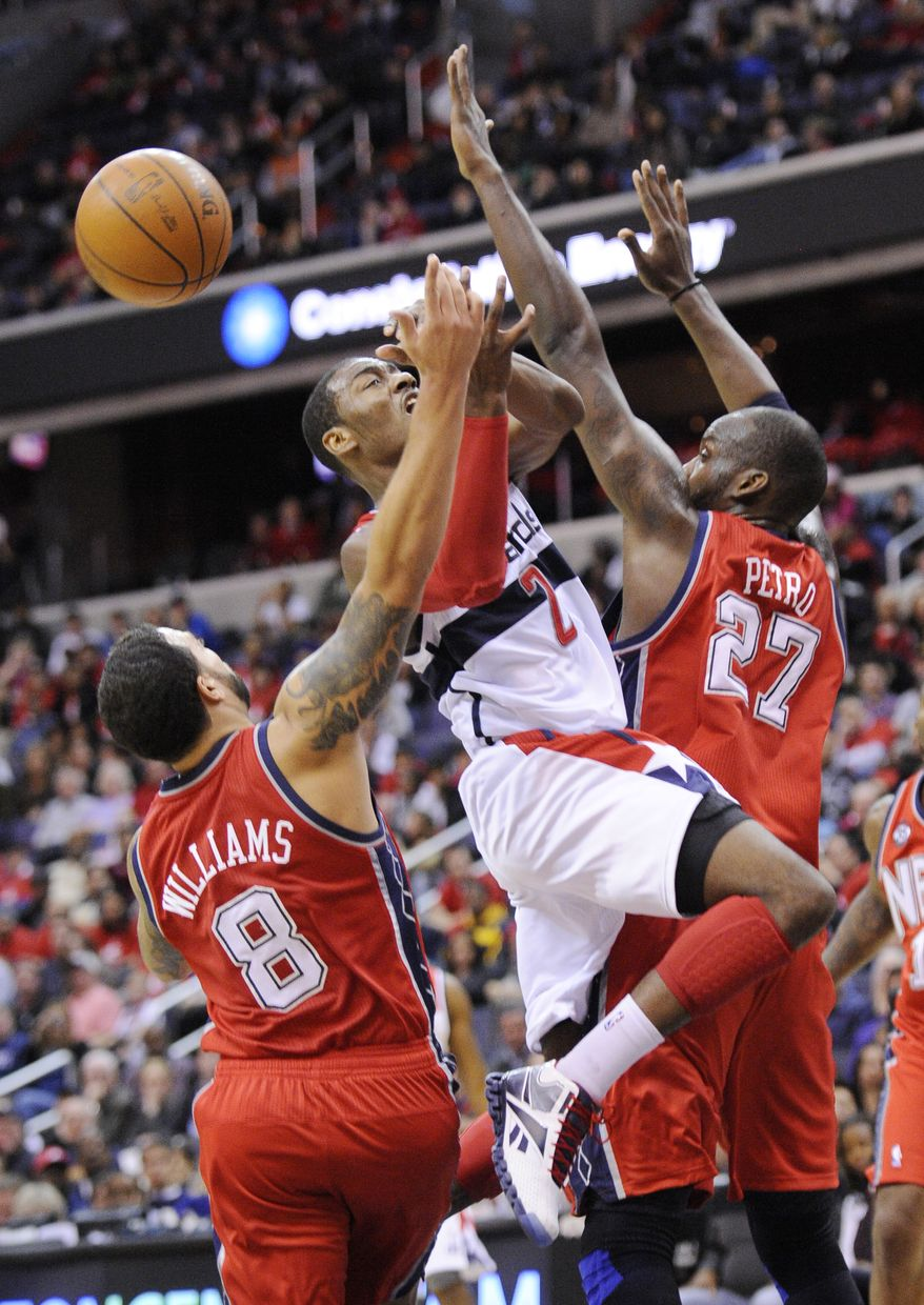 Washington Wizards guard John Wall (2) loses the ball while driving between New Jersey Nets' Deron Williams (8) and Johan Petro (27) during the second half of an NBA game Monday, Dec. 26, 2011, in Washington. The Nets won 90-84. (AP Photo/Nick Wass)