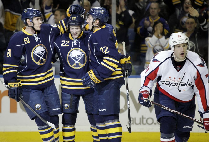 Buffalo Sabres' Brayden McNabb (81) celebrates his goal with Brad Boyes (22) and Luke Adam (72) as Washington Capitals' Brooks Laich skates away during the first period of an NHL game in Buffalo, N.Y., Monday, Dec. 26, 2011. The Sabres won 4-2. (AP Photo/David Duprey)