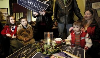 ** FILE ** Rep. Michele Bachmann, Minnesota Republican, autographs a campaign poster at Tangleberries in Centerville, Iowa, on Friday, Dec. 23, 2011, in her bid for the GOP presidential nomination. (AP Photo/Charlie Riedel, File)