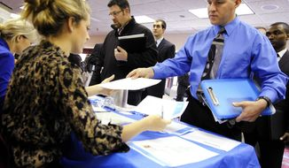 **FILE** Clarence Turner of Little Canada, Minn., hands in his resume Nov. 2, 2011, at the Minneapolis Career Fair in Bloomington, Minn., where he was looking for a hotel audit job. (Associated Press)