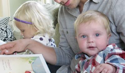 Matt Hammitt, lead singer for the Christian rock band Sanctus Real, reads a book to his 1-year-old son, Bowen, at their home. (Associated Press)