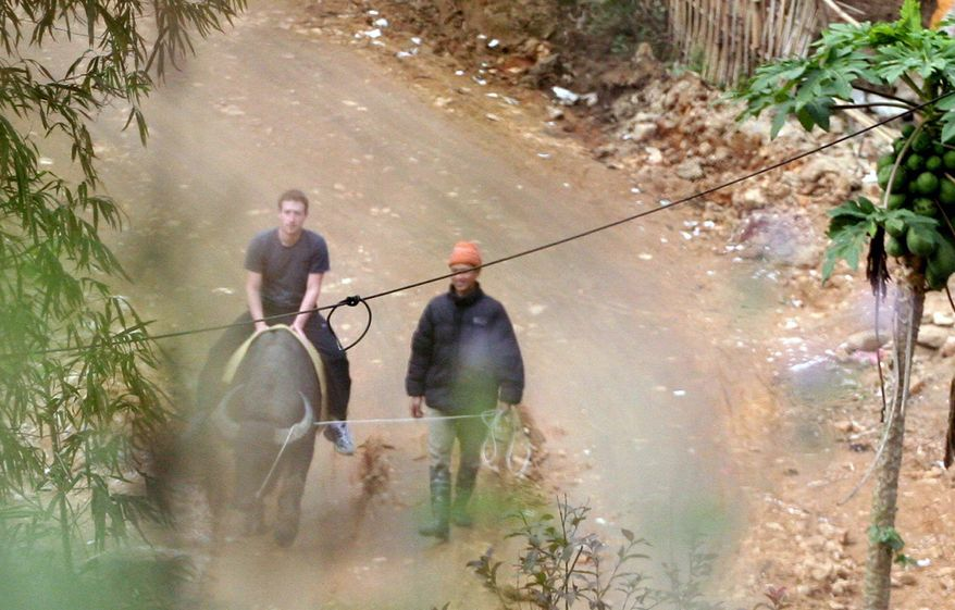 Facebook website founder Mark Zuckerberg rides a water buffalo in the northern resort town of Sapa in Vietnam where he vacationed last week. (VnExpress via Associated Press)