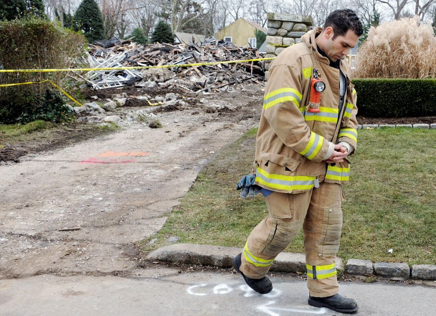 Firefighter Nick Tamburro pays respects outside the Stamford, Conn., home where a Christmas morning fire killed three girls and their grandparents. Officials said fireplace ashes in a bag started the fire that devoured the large Victorian house. (Associated Press)