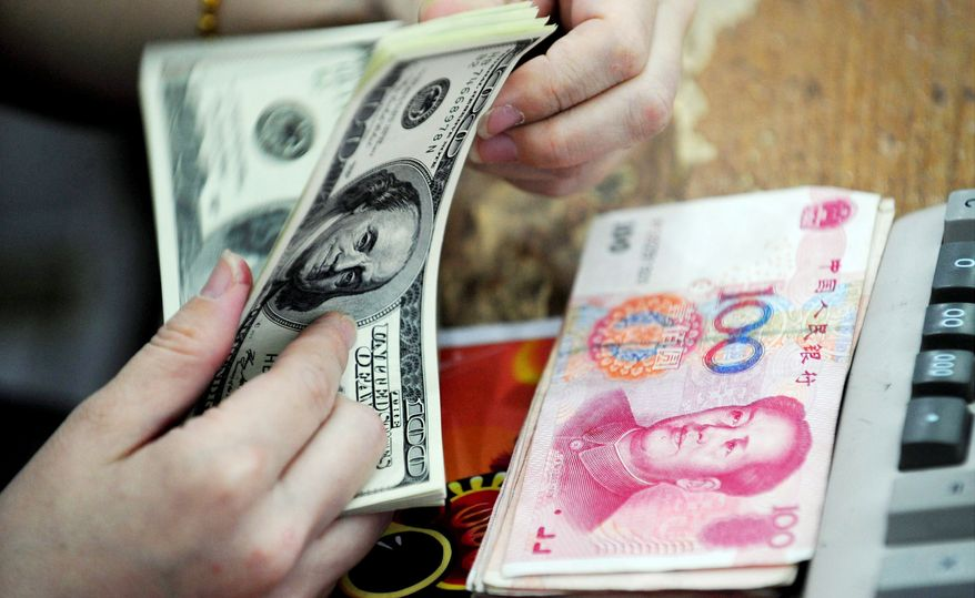 A Chinese clerk counts U.S. dollars in exchange for Chinese renminbi at a Hefei, China, bank. (Associated Press)