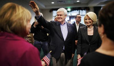 Republican presidential candidate and former House Speaker Newt Gingrich, accompanied by his wife Callista, makes a campaign stop Dec. 27, 2011, at the Dubuque Golf and Country Club in Dubuque, Iowa. (Associated Press)