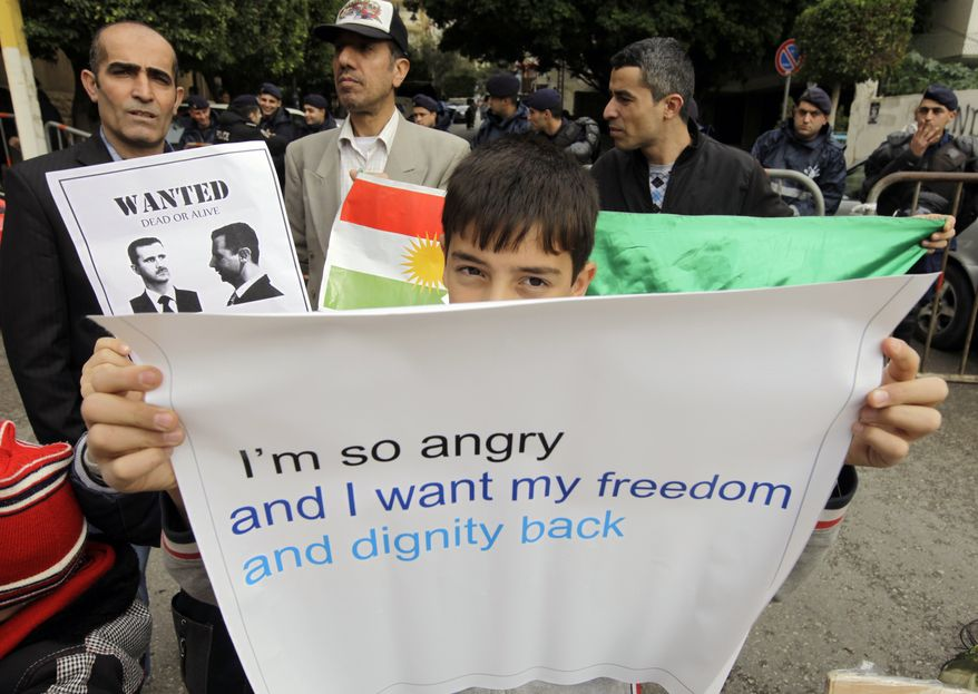 A Syrian Kurdish boy carries a banner during a protest outside the Arab League office in Beirut, Lebanon, Sunday, Dec. 25, 2011. The protesters said the Arab League was not serious in attempts to stop the Syrian regime crackdown. A man behind the boy was carrying a poster of President Bashar Assad of Syria. (AP Photo/Bilal Hussein)