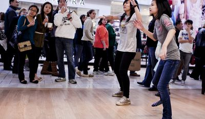 Kim Phan, 11, from right, and Sam Thai, 16, both of Annandale, Va., play a dancing game at an Xbox display in the Microsoft store as a crowd gathers to watch the two dance at the Tysons Corner Center mall in McLean, Va., on Dec. 26, 2011. (T.J. Kirkpatrick/ The Washington Times)