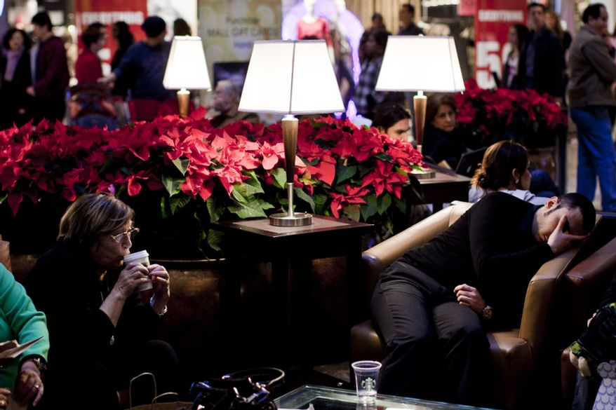 Widad Parsons, of Ashburn, Va., left, sips coffee while taking a break as a weary shopper naps nearby at the Tysons Corner Center mall in McLean, Va., on Dec. 26, 2011. The National Retail Federation projected this years' holiday sales to be up 3 percent over last year, but the Tysons mall is up 4 percent over last year's sales figures for the Black Friday to Christmas Eve period. (T.J. Kirkpatrick/ The Washington Times)