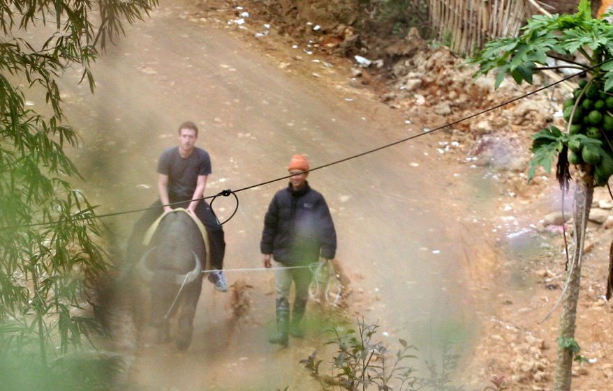 In this Dec. 26, 2011, photo, Facebook website founder Mark Zuckerberg rides a water buffalo in northern resort town of Sapa in Lao Cai province, Vietnam. (AP Photo/VnExpress, Le Thanh Hieu)
