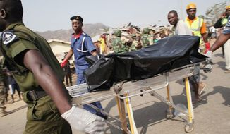 Above: Onlookers gather around the site of a bomb blast at St. Theresa Catholic Church in Madalla, Nigeria, on Christmas Day. A radical Muslim sect claimed responsibility for the attack and for another bombing near a church in the restive city of Jos. Below: Rescue workers remove the body of one of the victims. (Associated Press)